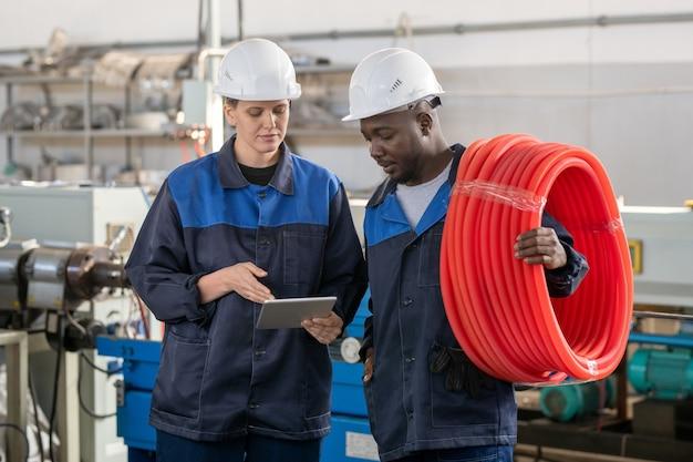 Rückansicht von industriearbeitern in orangefarbenen schutzhelmen, die über ein großes fabriklager nachdenken