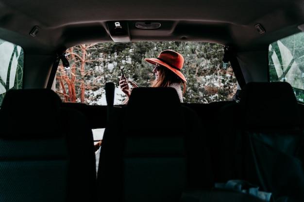 Rückansicht von innen ein auto der jungen frau im freien, das stilvollen hut trägt. schneebedeckter berg