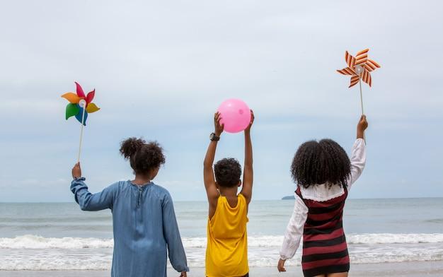Rückansicht von jungen kindern, die farbballons und regenbogenwindmühle halten, die am strand gehen.