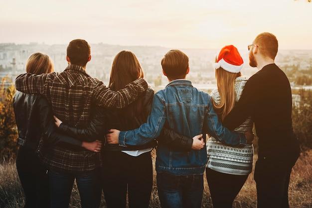 Rückansicht von jungen männern und frauen, die einander umarmen und die moderne stadt betrachten, während weihnachten zusammen feiern