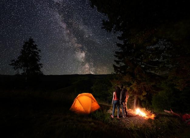 Rückansicht von jungen paartouristen, die den sternenhimmel genießen