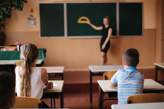 Rückansicht von kindern, die im klassenzimmer sitzen und studieren. grundschule