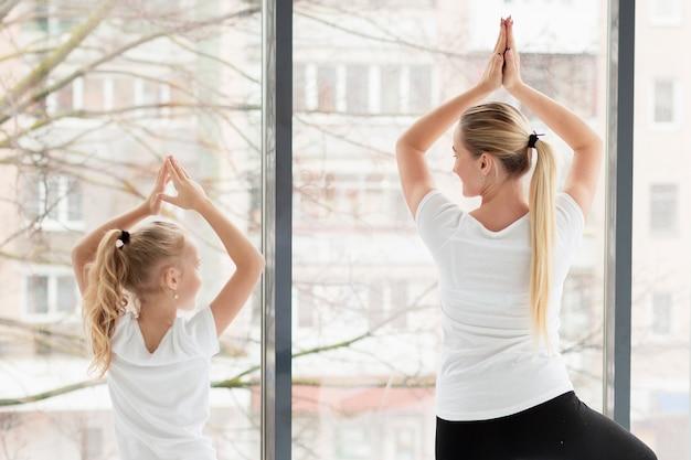 Rückansicht von mutter und tochter in yoga-pose