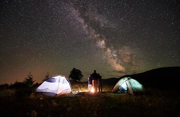 Rückansicht von mutter und zwei söhnen rucksacktouristen, die auf dem campingplatz in den bergen ruhen, neben dem lagerfeuer und zwei beleuchteten zelten stehen und den nachthimmel voller sterne betrachten, milchstraße