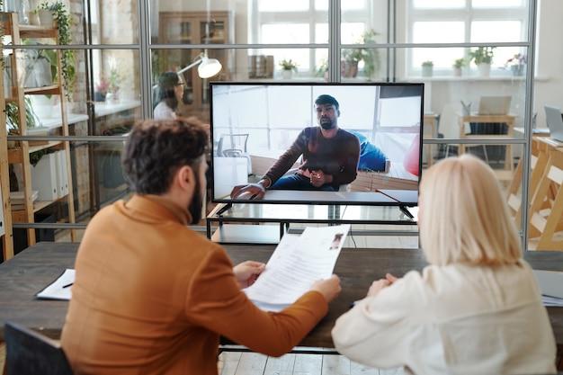 Rückansicht von personalmanagern, die am tisch im großraumbüro sitzen und den computer benutzen, während sie den kandidaten online interviewen