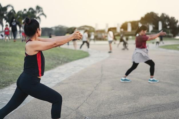 Rückansicht von reifen, gesunden menschen, die abends nach der arbeit im stadtpark aerobic tanzen, um sich zu entspannen und ein gesundes leben zu führen. sport und erholung