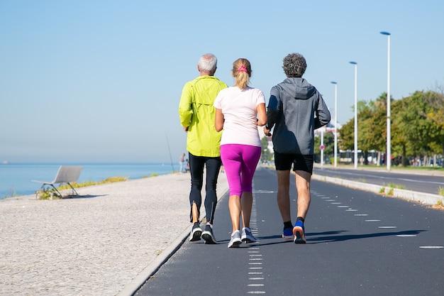 Rückansicht von reifen joggern in sportkleidung, die auf spur entlang flussufer laufen. kopierraum in voller länge. aktivitäts- oder lebensstilkonzept
