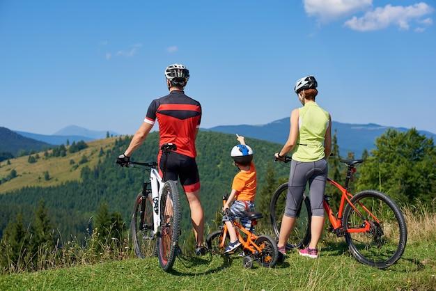 Rückansicht von touristischen familienbikern, mama, papa und kind, die mit fahrrädern auf grasbewachsenem hügel stehen und schönen blick auf die berge genießen. junge zeigt in die ferne