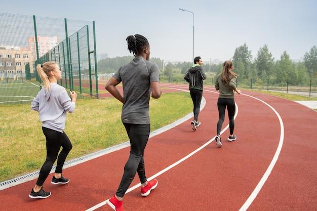 Rückansicht von vier jungen interkulturellen menschen in aktivkleidung, die während des marathons die rennstrecken des freiluftstadions hinunterlaufen