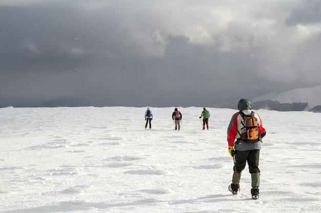 Rückansicht von wanderern, die auf schneebedecktem hügel in den winterbergen gehen.