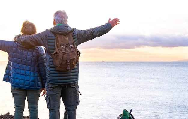 Rückansicht von zwei älteren leuten, die den meerblick und die freiheit bei sonnenuntergang genießen. auf der klippe stehend mit blick auf den horizont über wasser
