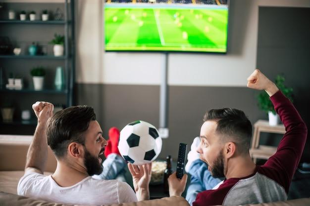 Rückansicht von zwei besten freunden und fußballfans, die sich ein sportspiel im fernsehen ansehen, bier trinken und snacks essen, während sie das team auf der couch anfeuern