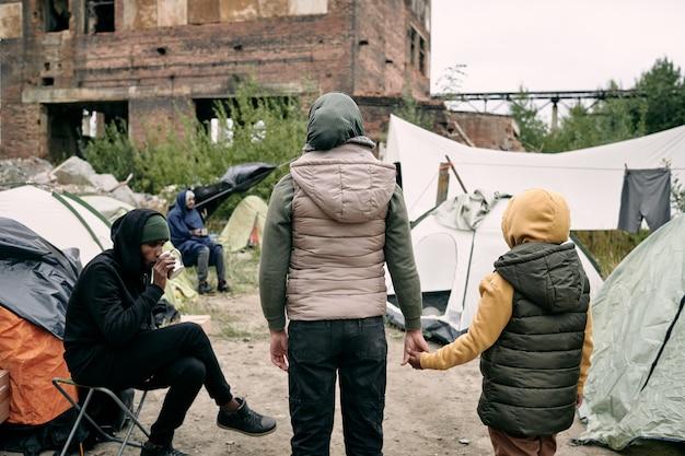 Rückansicht von zwei flüchtlingen, die vor dem lager stehen