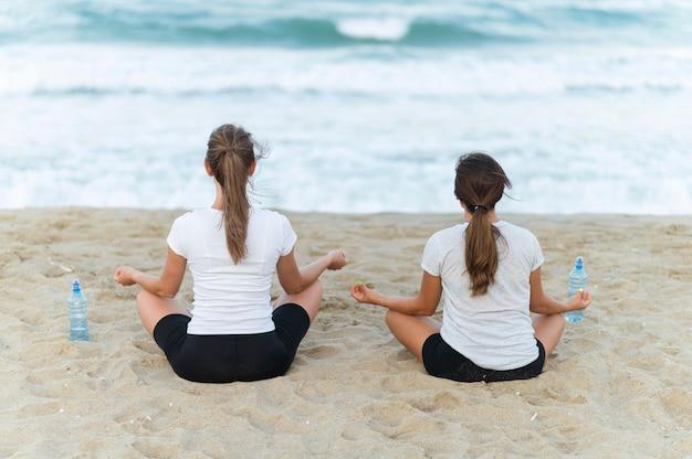 Rückansicht von zwei frauen, die yoga am strand tun