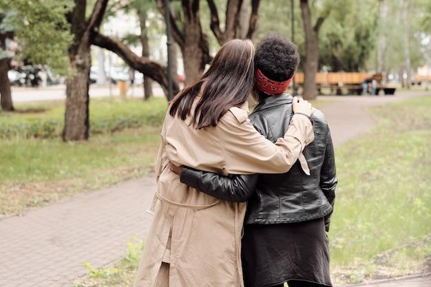 Rückansicht von zwei jungen frauen in freizeitkleidung, die im park spazieren gehen