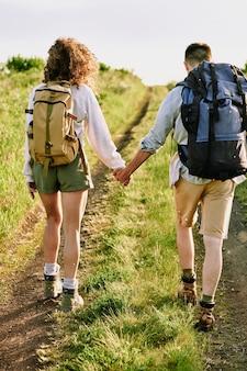 Rückansicht von zwei jungen liebevollen wanderern mit rucksäcken, die von händen halten, während sie die landstraße herunterkommen, die von grünem gras bedeckt ist