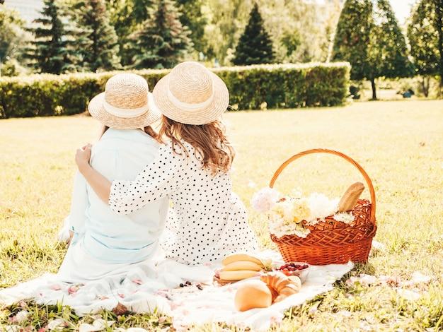 Rückansicht von zwei jungen schönen lächelnden hippie-mädchen in trendigem sommerkleid und hüten. frauen, die draußen picknick machen.