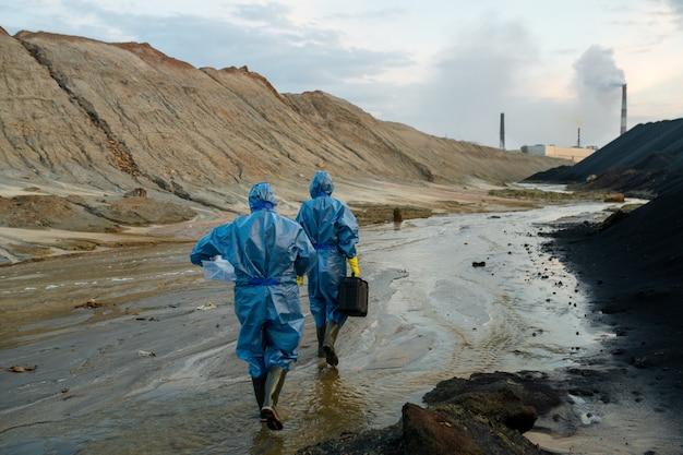 Rückansicht von zwei jungen zeitgenössischen wissenschaftlerinnen in blauen schutzhüllen und gummistiefeln, die sich auf schmutzigen straßen und großen pfützen bewegen
