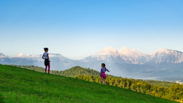 Rückansicht von zwei kindermädchen, die auf einer bergwiese stehen, jüngeres, das auf das tal unten zeigt