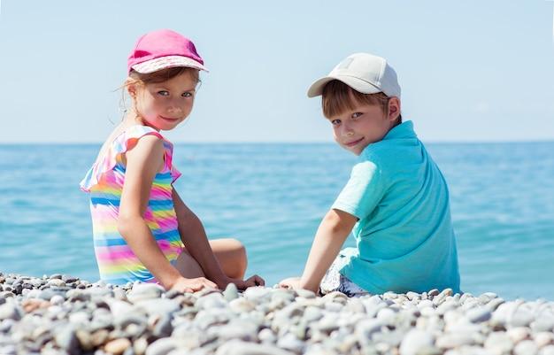 Rückansicht von zwei kindern, die auf steinen sitzen. kleine reisende in der nähe des ozeans. sommerferienkonzept. reisehintergrund