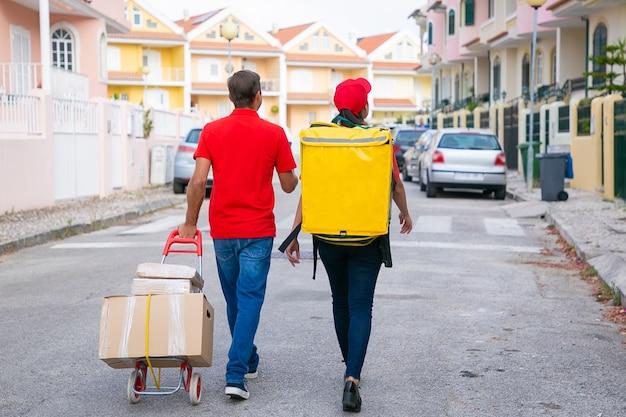 Rückansicht von zwei kurieren, die mit kisten auf wagen gehen. zusteller liefern thermo-rucksack und tragen rotes hemd oder mütze. lieferservice und online-shopping-konzept