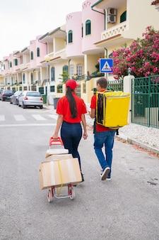 Rückansicht von zwei postarbeitern, die mit thermotasche und kisten auf wagen gehen. professionelle kuriere, die gemeinsam bestellungen liefern.