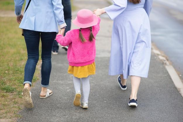 Rückansicht von zwei weiblichen mütterschwestern, die spazieren gehen und ein kleines mädchen tragen