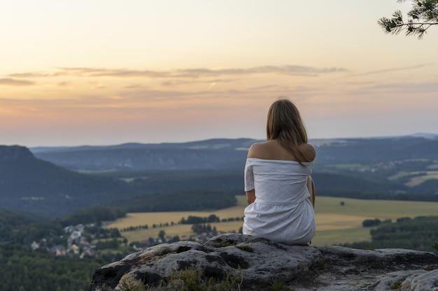Rückansichtaufnahme einer jungen frau, die am rand einer klippe sitzt und einen majestätischen sonnenuntergang genießt