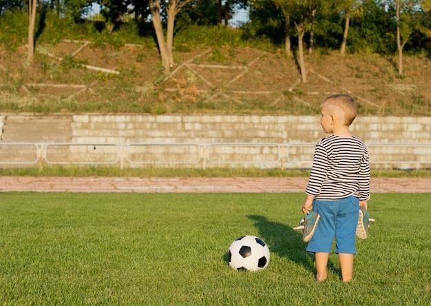 Rückansichtbild eines kleinen barfußjungen, der mit seinen schuhen in seinen händen neben einem fußball auf grünem gras steht