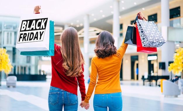 Rückansichtfoto von zwei jungen frauen in den bunten kleidern mit einkaufstaschen in den händen mit druck auf ihm vom schwarzen freitag.