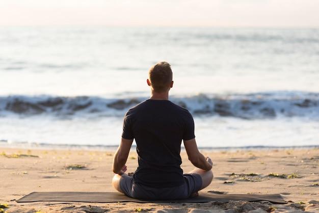 Rückansichtmann, der yoga auf sand tut