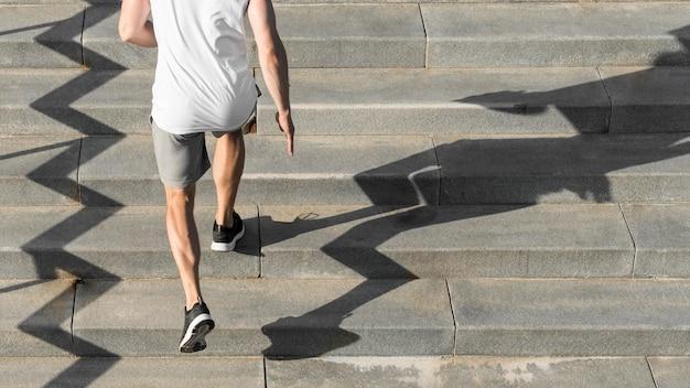 Rückansichtmann läuft auf treppen mit kopienraum