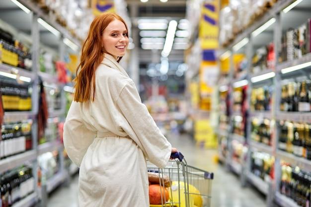Rückansichtporträt der kaukasischen frau, die wagen im supermarkt in der abteilung des alkohols hält. einkaufen genießen