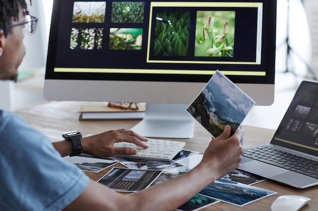 Rückansichtporträt des jungen afroamerikanischen mannes, der gedruckte fotografien unter verwendung der bearbeitungssoftware über computer hält, während am schreibtisch im heimbüro, kopierraum arbeitet