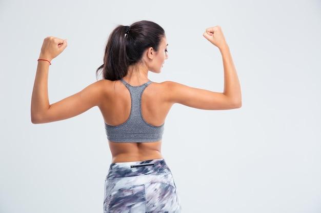 Rückansichtporträt einer fitnessfrau, die ihren bizeps lokalisiert auf einer weißen wand zeigt