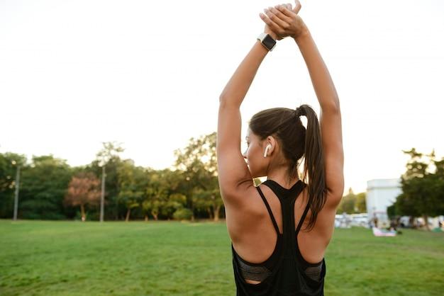Rückansichtporträt einer fitnessfrau in den kopfhörern, die sich strecken