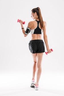 Rückansichtporträt einer schlanken fitnessfrau in voller länge