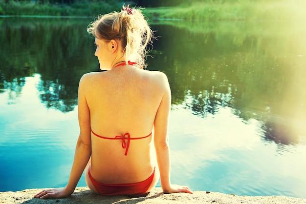 Rückansichtporträt einer ziemlich entspannten frau am sonnigen strand mit blauem wasserhintergrund. koloriertes bild