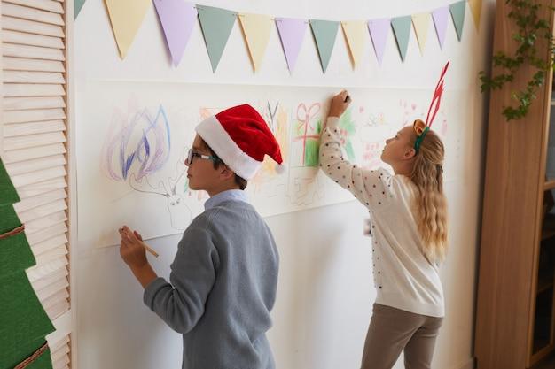 Rückansichtporträt von jungen und mädchen, die an wänden zeichnen, während sie weihnachtsmützen und geweih für weihnachten tragen, kopieren raum