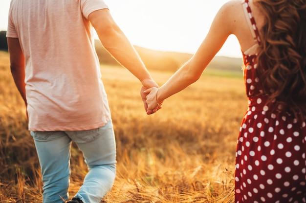 Rückansichtsfoto eines schönen paares, das bei einem schönen sonnenuntergang auf einem feld hand in hand geht