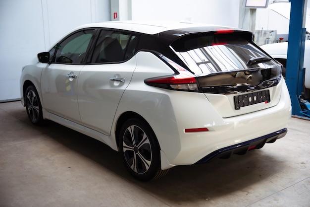 Rückansichtsfoto eines weißen elektroautos, das auf dem reparaturstationsservice steht