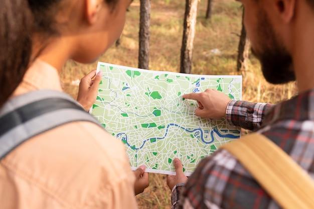 Rückansichtspaar, das auf einer karte schaut