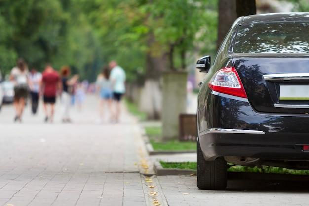 Rückansichtsteil des glänzenden schwarzen luxusautos geparkt auf stadtfußgängerzonenpflaster auf hintergrund der unscharfen silhouetten von leuten, die entlang grüner sonniger sommergasse gehen. modernes lifestyle-konzept.