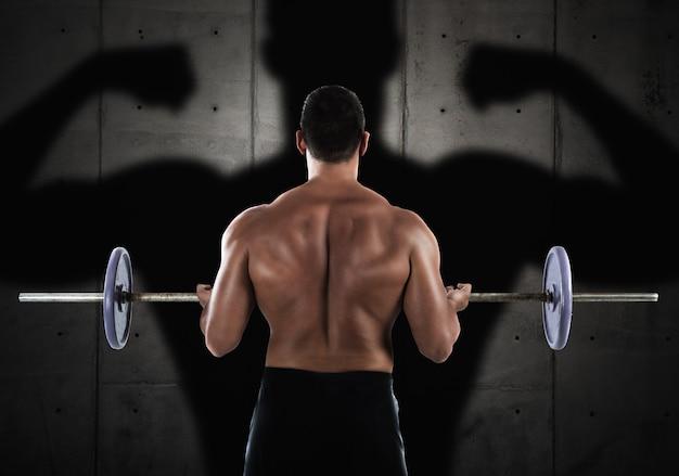 Rücken des muskulösen mannes, der mit einer langhantel trainiert