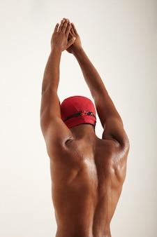 Rücken und arme eines muskulösen afroamerikaner-schwimmers in roter mütze und schwarzer schutzbrille mit ausgestreckten armen in der luft, die sich darauf vorbereiten, isoliert auf weiß zu tauchen.