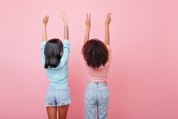 Rücken von brünetten mädchen in jeans. glamouröse dunkelhaarige damen in vintage-kleidung posieren mit erhobenen händen.