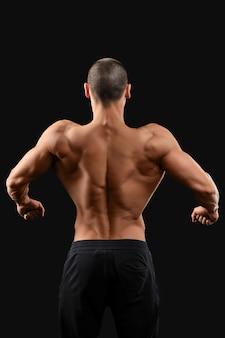Rückenarbeit. männlicher bodybuilder, der seinen getönten muskulösen rücken zeigt, der auf dunkelheit aufwirft