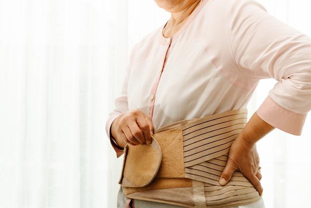 Rückenschmerzen, ältere frau, die rückseitigen stützgurt auf weißem hintergrund trägt