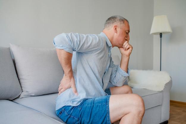 Rückenschmerzen. nahaufnahme des reifen mannes, der spinal- oder nieren-schmerz hat,