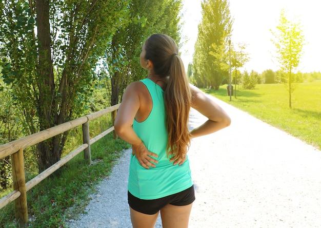 Rückenschmerzen. sportliche laufende frau mit rückenverletzung in sportbekleidung, die die unteren rückenmuskeln berührt, die draußen im park stehen.